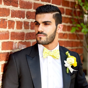 Groom in Black Tuxedo with Yellow Bow-Tie and Boutonniere