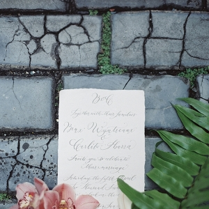 Calligraphy on a Wedding Invitation Surrounded by Flowers