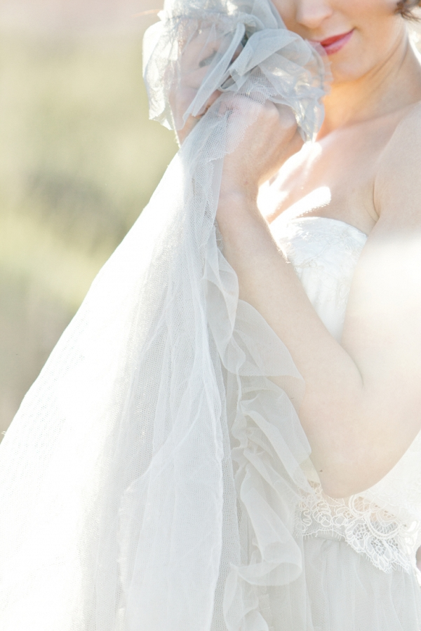 chantalle holds the layers of tulle from her beautiful dress against her cheek