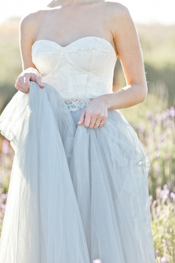 beautiful tulle skirt of the dress held in her hands as she walks through the Lavender