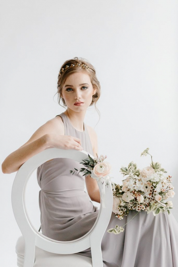 bridesmaid seated on a white chair holding a bouquet of flowers