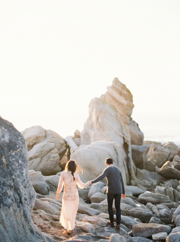 Engaged couple frolicking in the rocks at Big Sur