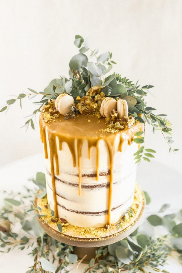 wedding cake topped with foliage and macarons