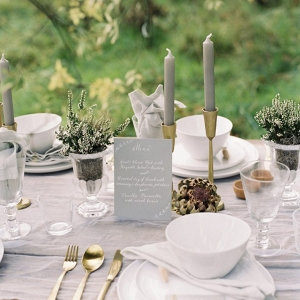 tablescape with tall taper candles white tableware and grey accents