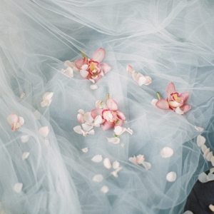 scattering petals and orchids upon the tulle wedding dress