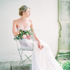 bride sat on a chair decorated with flowers
