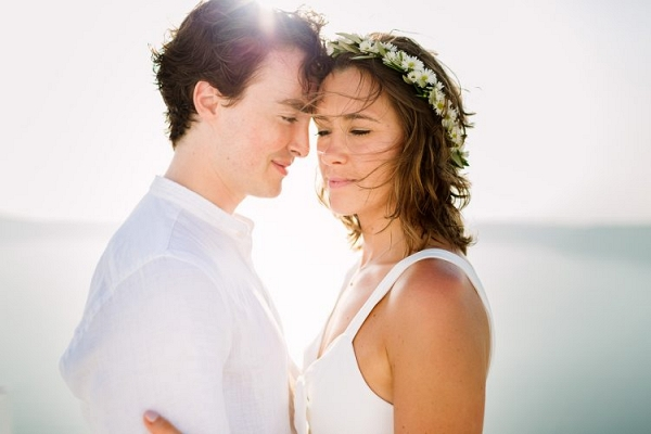 Couple tenderly touch heads with the sunlight streaming through