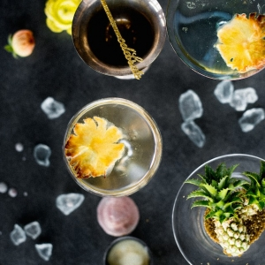 Drinks with mini pineapples and gold glitter stir sticks