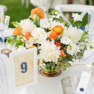 Eclectic orange and white centerpiece with simple table number