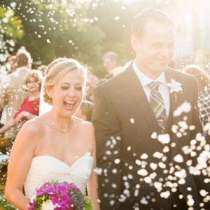 Petals being thrown as couple heads down the aisle