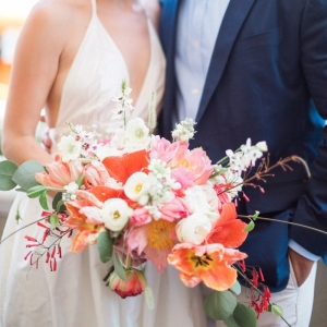 Bride and groom with coral bouquet