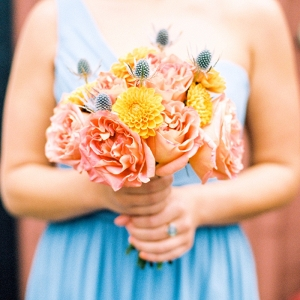 Pale blue bridesmaid with peach and orange bouquet