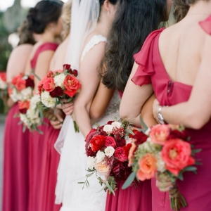 Bride and bridesmaids with red and white flowers