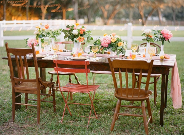 Outdoor Wedding Reception Decor with Vintage, Mis-Matched Wooden Chairs and Orange, Yellow and Pink Wedding Centerpieces with Cafe Lighting
