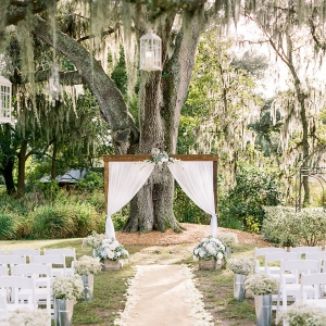 Rustic Outdoor Wedding with White Draped Altar and White Folding Chairs
