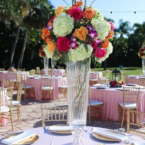 Outdoor Wedding Reception Décor with Gold Chiavari Chairs, Pink Linens and Orange, Bright Pink and Fuchsia Floral Centerpieces with Lanterns and Market Twinkle Lights