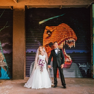 St. Petersburg Bride and Groom Wedding Portrait with Graffiti Backdrop in Ivory Strapless Sweetheart Wedding Dress and Cascading Purple and White Wedding Bouquet