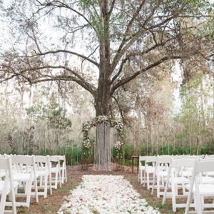 Rustic Outdoor Wedding Ceremony with Light Pink and White Floral Archway under Tall Pines with White Resin Folding Chairs and Rose Petal Aisle