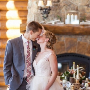 Couple kisses in front of a fireplace at a ski lodge