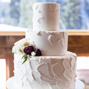 simple butter cream wedding cake with 3 tiers and burgundy and ivory ranunculus