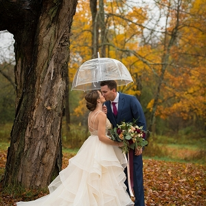 Romantic kiss under an umbrella on a beautiful autumn day