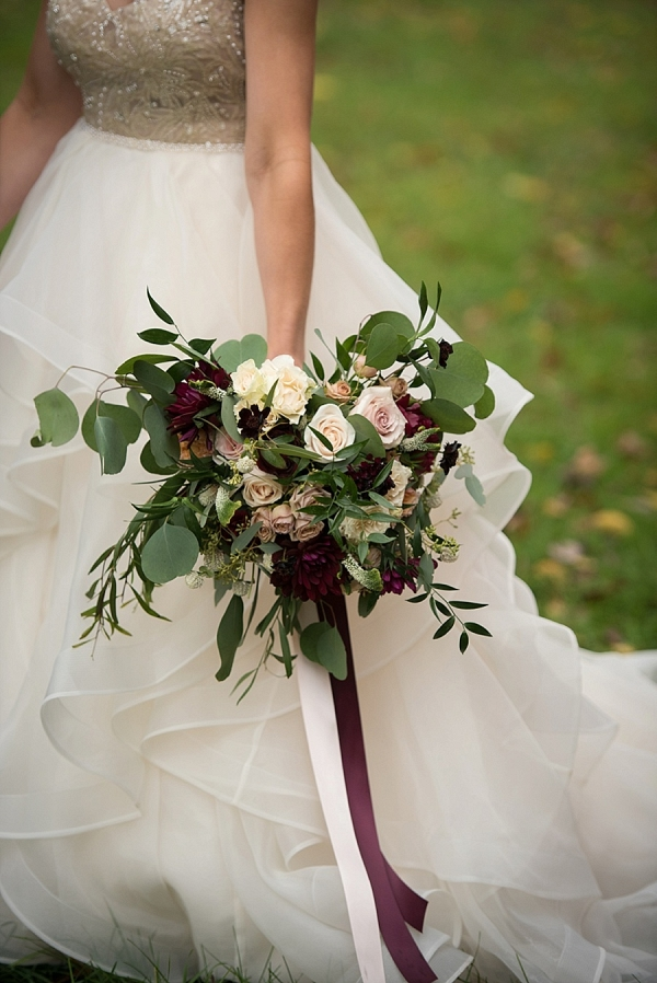 Ivory and burgundy bouquet with a gold and white wedding gown