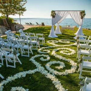 Romantic lakefront ceremony with flower petal designed aisle