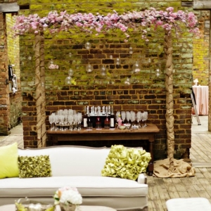 Outdoor vintage lounge area with bar and floral arch