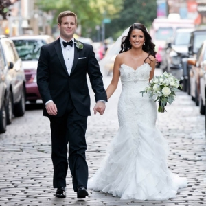 Bride and groom walking on cobblestone street in New York