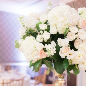 Elegant tall floral centerpieces with Christmas ornament-filled vases