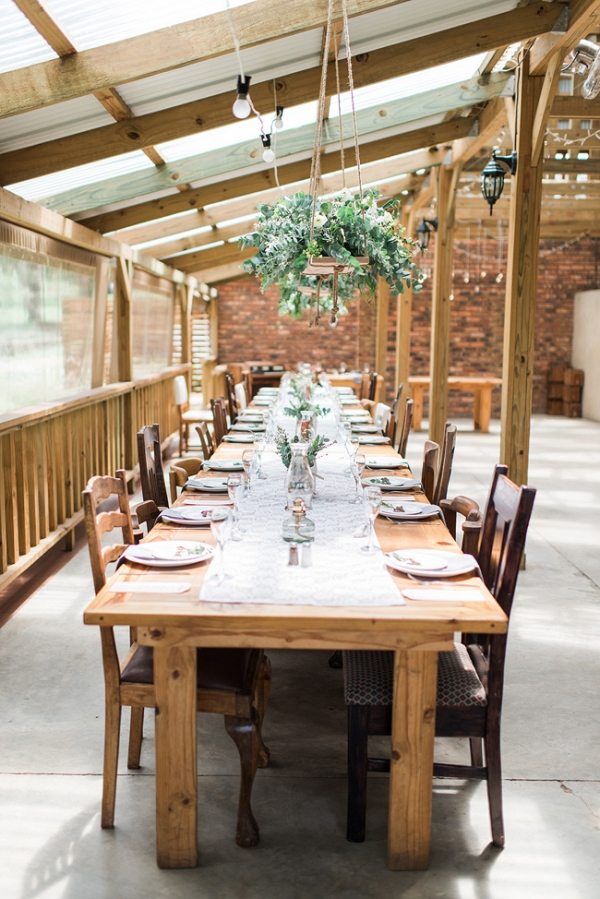 Long wooden tables with hanging greenery