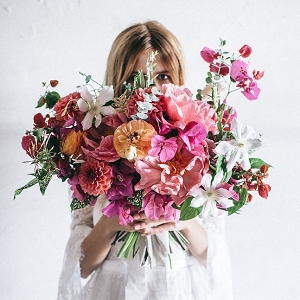Bride holding large loose pink floral bouquet