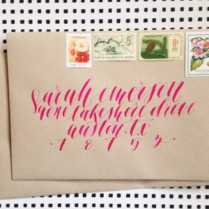 Whimsical and modern wedding calligraphy in fuchsia ink on kraft paper