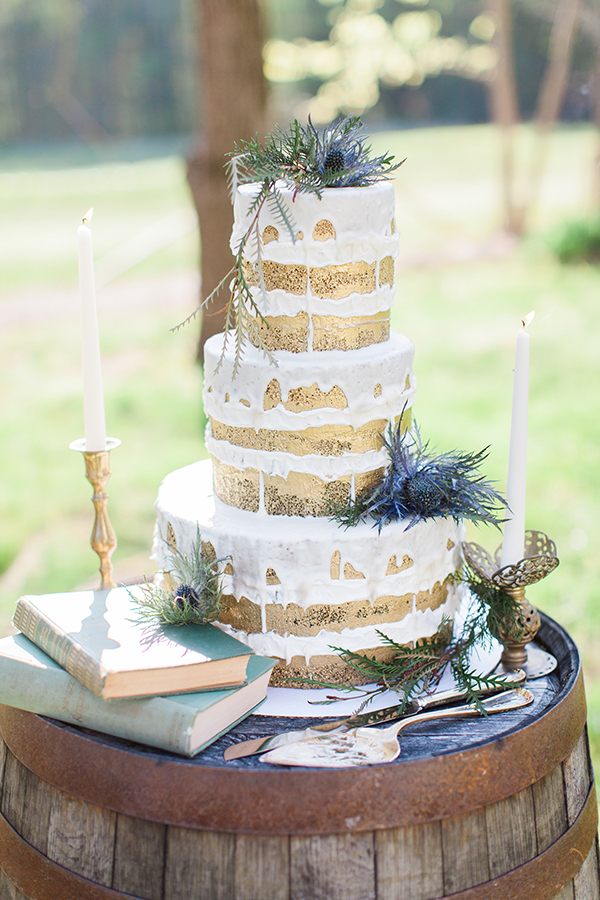 Gold-brushed naked cake accented with blue thistles