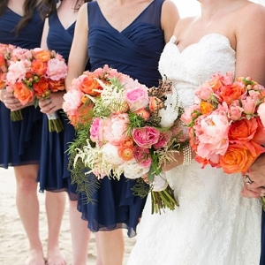 Navy blue bridesmaid dresses and coral bouquets
