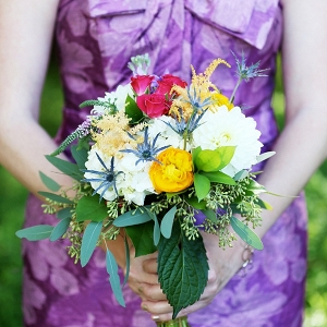 Colorful bridesmaid bouquet with purple patterned dress