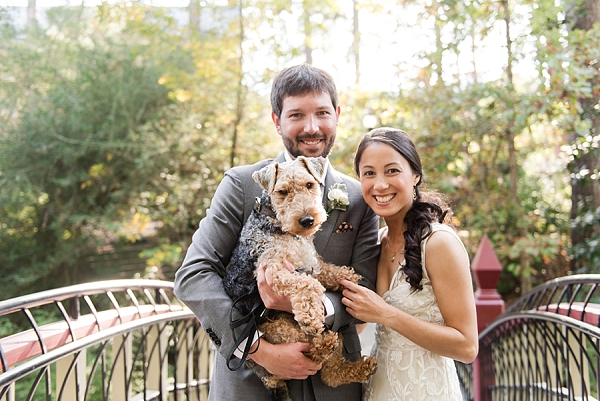Bride and groom holding their dog