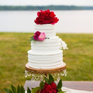 Tiered white wedding cake with peony cake topper