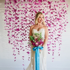 Bride in front of paper flower backdrop