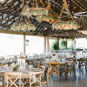 Wedding reception with greenery covered chandeliers