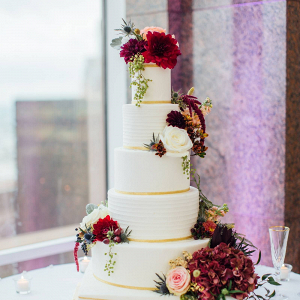 Classic white wedding cake with burgundy florals