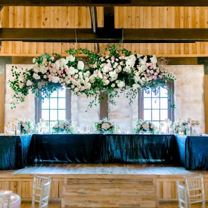 Head table at wedding with giant floral chandelier