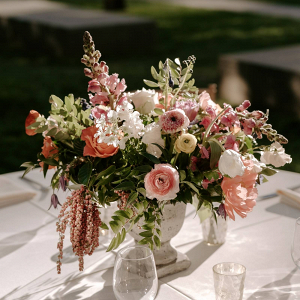 Peach floral centerpiece in stone urn