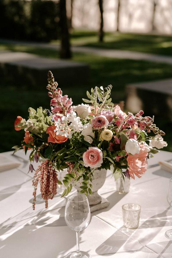 Peach floral centerpiece in stone urn
