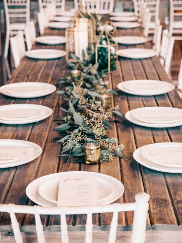 Rustic wedding tablescape with greenery runner and lanterns
