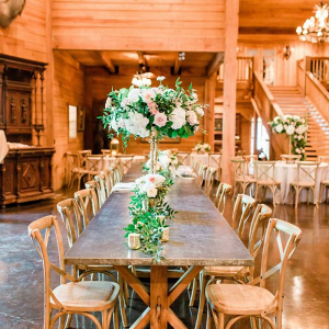 Lodge wedding reception with tall pink and white floral centerpieces