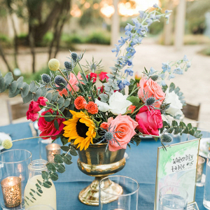 Colorful floral centerpieces in gold urns