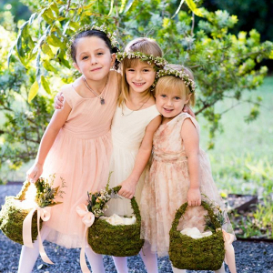 Flower girl in flower crowns with moss baskets