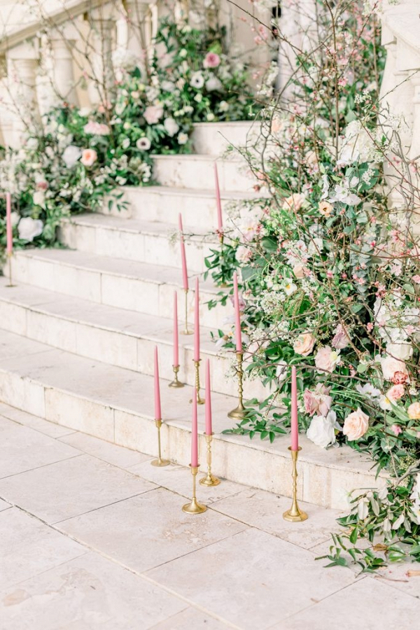 Staircase covered in florals and pink taper candles