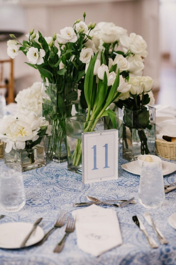 Modern wedding centerpiece with monochromatic florals and printed linens